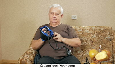 Man aged overweight measures the pressure of their own home on the couch. He listens to pulse through sphygmomanometer