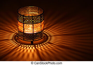 Old-style candlestick with flaming candle inside in the dark...