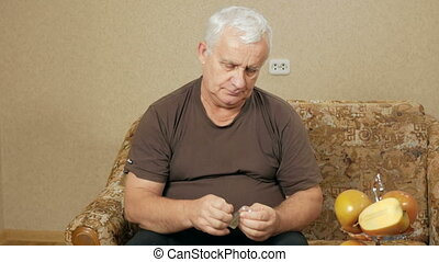 Sick senior overweight man taking pills in house on a sofa and drinks water in a glass. He makes several smooth liquid. The concept of health in the elderly