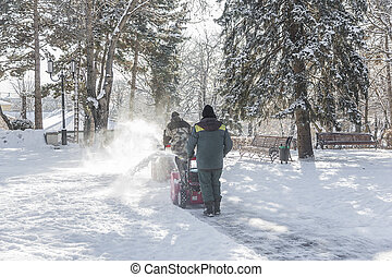Snow removal in the city park. - Workers are clearing the...