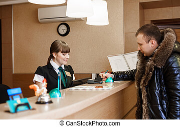 Male guest at hotel reception during check-in - Side view of...