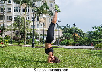 Beautiful slim sporty young woman doing handstand or...