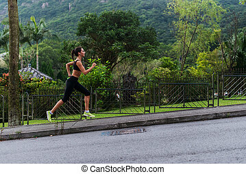 Young fit woman doing cardio exercise, listening to music,...