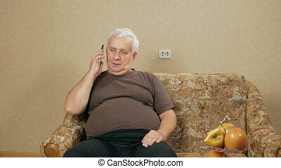 The man at the age of talking on a cell phone at home on the couch. His facial expression changed. communication concept