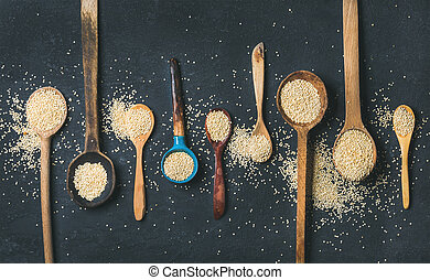 Quinoa seeds in different spoons over black stone...