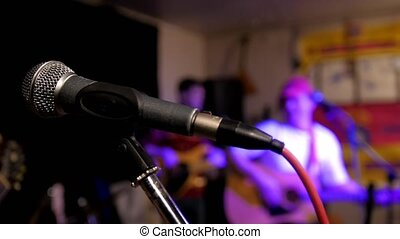 Microphone. Rock band playing musical instrument at concert,...