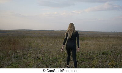Beautiful girl walking in a field.