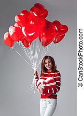 Woman with heart shaped balloons