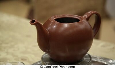 clay teapot with hot tea on a heated base steaming.