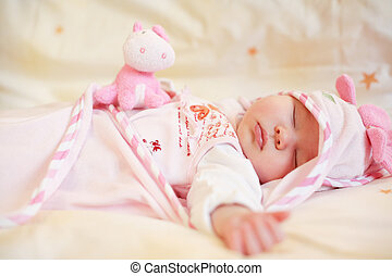 Sleeping baby - Lying sleeping baby with small teddy bear on...