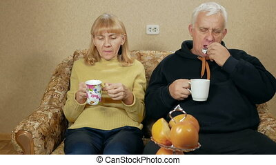 Elderly couple drink tea and eat sweets. Husband and wife...