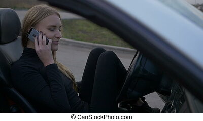 Beautiful girl talking on the phone in the car.