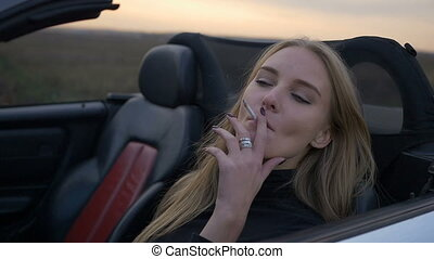 Young girl smoking in a convertible.