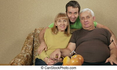 Young son of an elderly couple hugging at home on the couch. Everyone looks at the camera and smile. They communicate with each other and laugh. happy family concept.