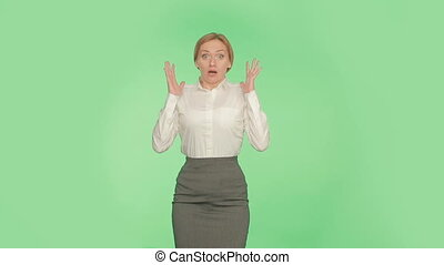girl covering mouth with her hands. green background....
