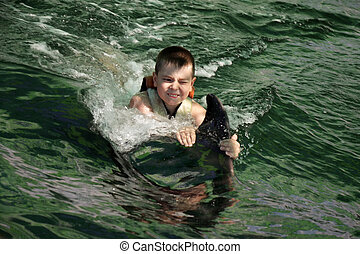 Boy swimming with dolphin closeup - Boy swimming with...