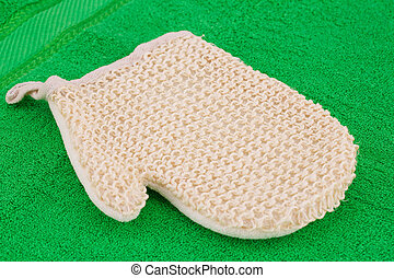 Glove massager on green towel, closeup picture.