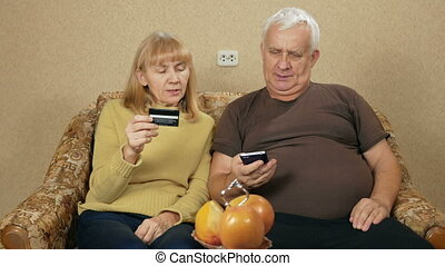 Senior couple pay for purchases in the Internet by bank credit card. Woman dictates the number, a man enters the information into the phone.