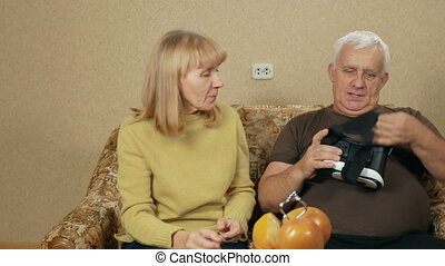 Elderly couple tries glasses virtual reality at home. The...