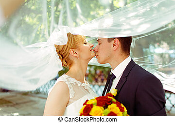 Groom touches bride's chin tenderly standing under her veil