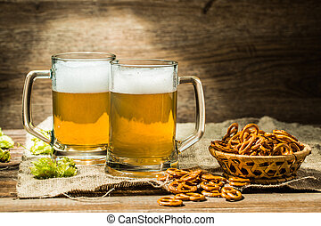 Two glasses of beer froth with hop and pretzels