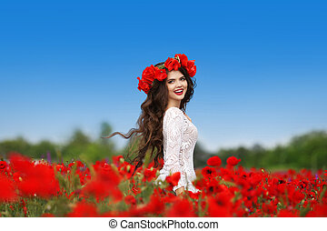 Beautiful carefree brunette woman with long healthy hair running on red poppies field