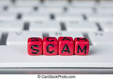 Scam word on the white keyboard showing swindles and fraud