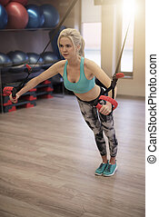 Attractive woman exercising on TRX