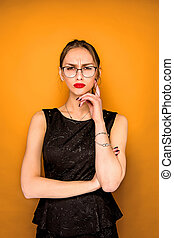 The young woman's portrait with wary emotions on orange...