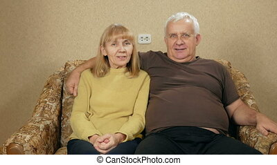Elderly couple resting at home on the couch and looking at the camera. They are smiling. The husband hug his wife.