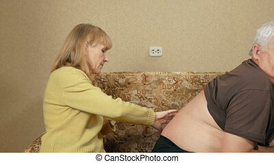 Senior woman rubs ointment for back pain man overweight....