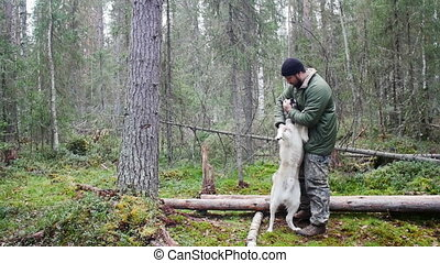 Man with his dog playing in forest