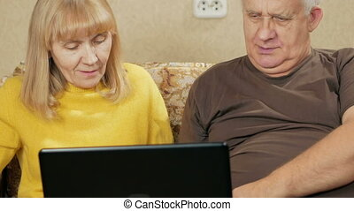 Mature couple resting a laptop on the couch at home. Husband and wife are browsing the news on the computer screen. holiday home concept.