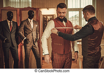 Tailor measuring client for custom made suit tailoring.