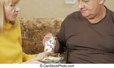 Elderly couple drink tea and eat sweets. Husband and wife sitting at home on the couch and relax. holiday home concept