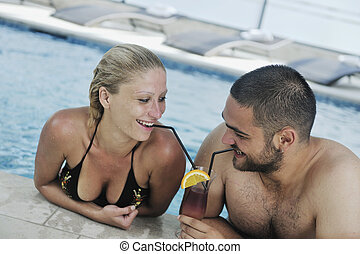 happy cople relaxing at swimming pool - happy young couple...