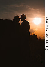 silhouettes of man and woman on a background the sun field -...