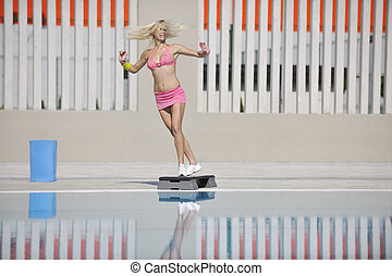fitness exercise at poolside - young beautiful healthy woman...