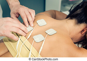 Therapist positioning TENS electrodes for treatment of back...