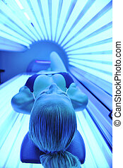 solarium treatment - young woman at laying on solarium bed...