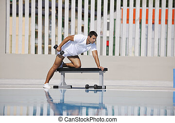 young man exercise at poolside - young healthy athlete man...
