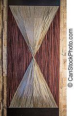 Sconces like hourglass. Located on a beige masonry.