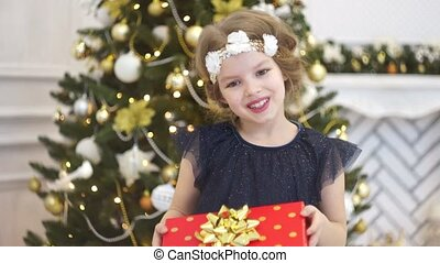 Boxing day. Cute little girl presents a Christmas gift. She...