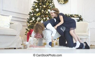 The father plays with children near the Christmas tree.
