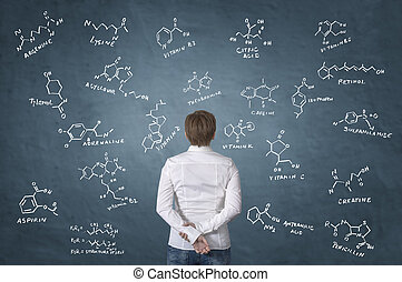 Healthcare worker standing in front of chemistry formula of...