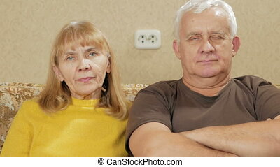 Elderly couple resting at home on the couch and looking at the camera.