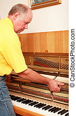 Piano tuner - Photo of man tuning piano