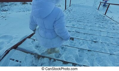Girl child goes down the stairs covered with snow. Child is walking in the park. Winter frosty day