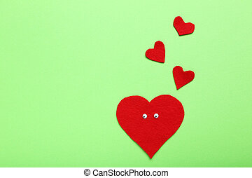 Red heart with googly eyes on a green background