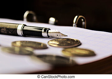 pen and notebook - fourtain pen and coins on the notebook